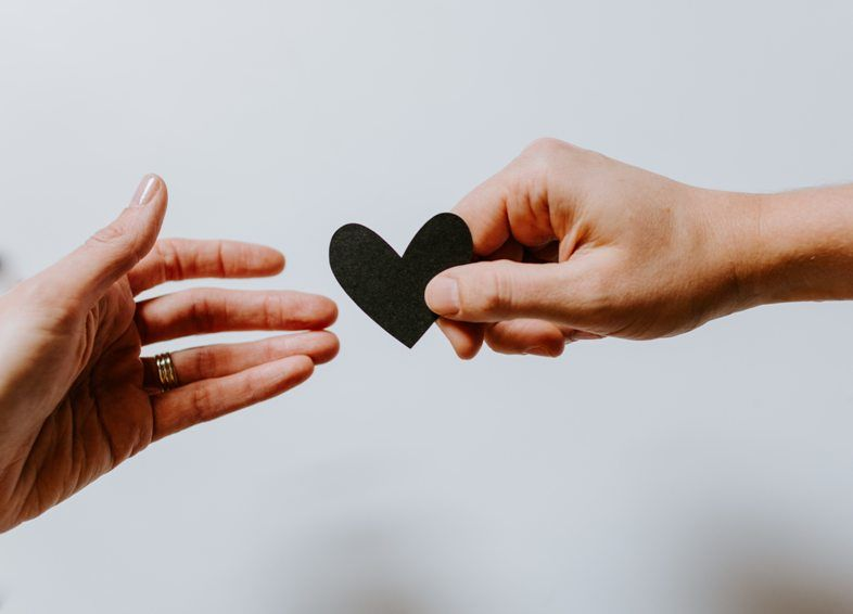 Black paper heart being handed form one person's hand to another