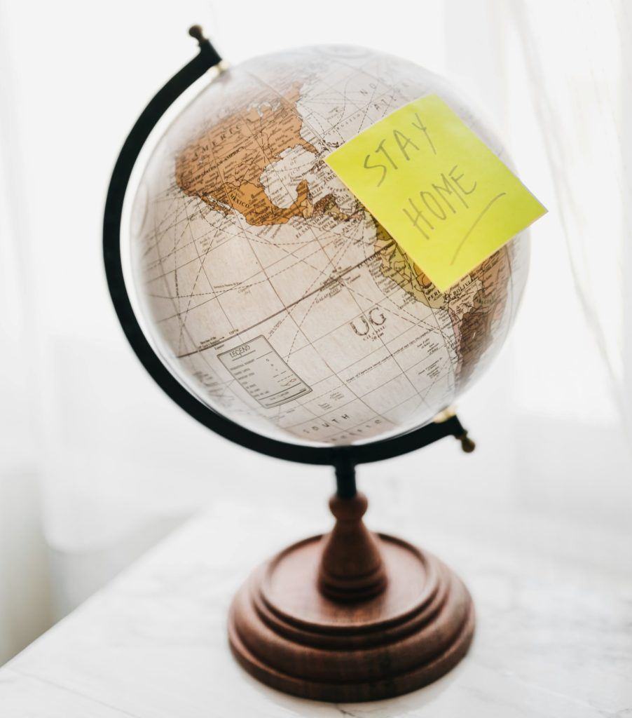 "Globe with yellow sticky note ""stay home"""